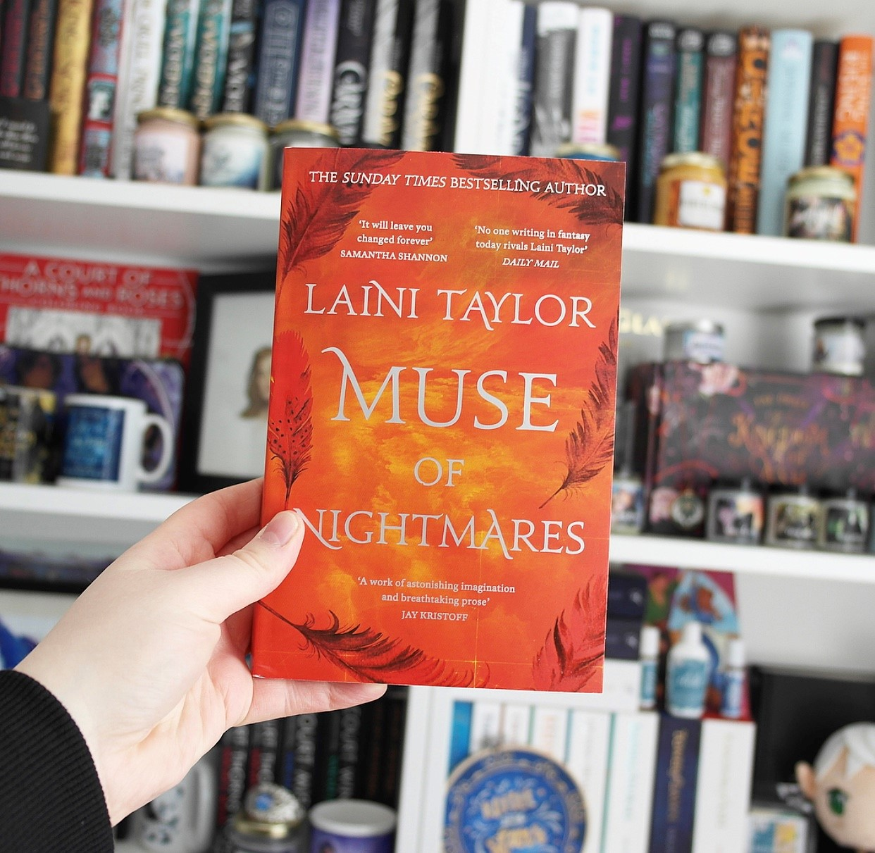 The red paperback edition of Muse of Nightmares is held in front of Amy's bookcases.