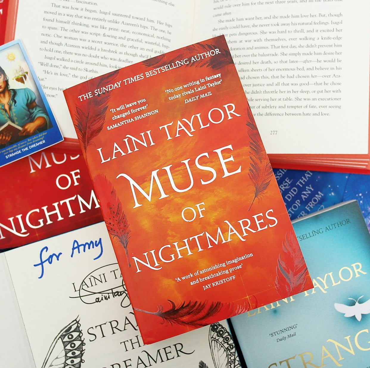 The paperback edition of Muse of Nightmares is lay on a collection of Laini Taylor books including the open Muse of Nightmares, the signed hardback edition of Strange the Dreamer and the paperback edition of Strange the Dreamer. There is also a sticker of Lazlo Strange.