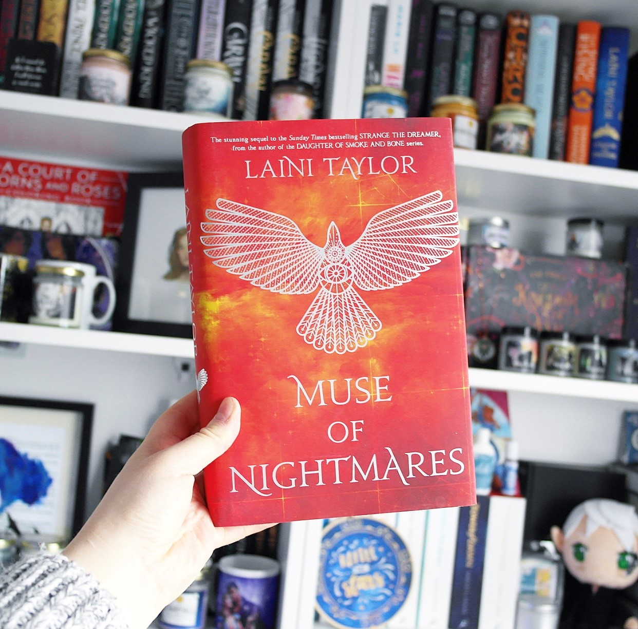 The red hardback edition of Muse of Nightmares held in front of Amy's bookcase, which is filled with books.